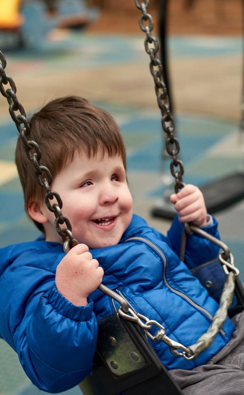 Boy wearing bright blue jacket on a swing