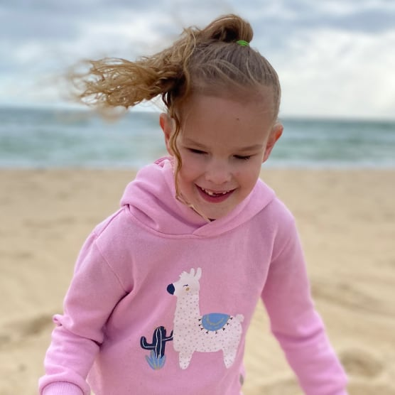 A young girl smiling at the beach