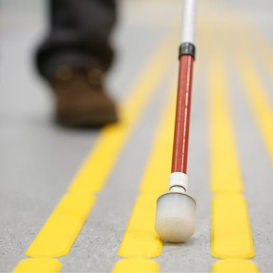 A White Tip cane on yellow tactile paving