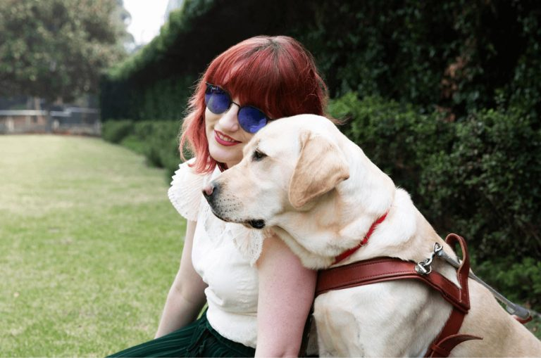 A person and a yellow Guide Dog, in harness, sitting on grass outside. The person is smiling at the camera and the Guide Dog is a profile view.